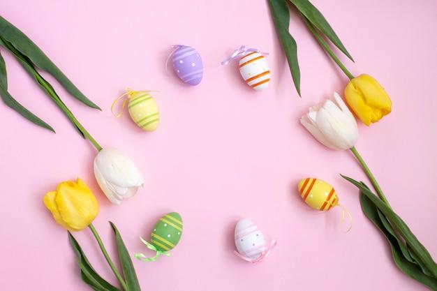 Ovos de páscoa de cor e tulipas amarelas brancas em um fundo rosa. Foto Premium