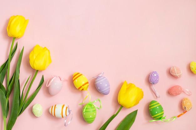 Ovos de páscoa de cor e tulipas amarelas brancas em um fundo rosa.