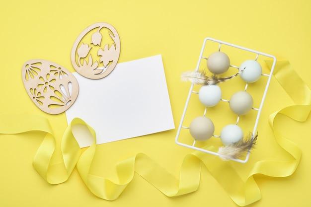 Ovos de páscoa de luz azul no suporte de metal vintage branco com penas, fita e papel em branco para texto em fundo amarelo. vista do topo.