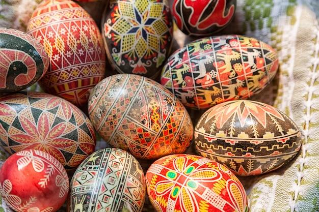 Ovos de páscoa de madeira em padrões russos antigos nacionais em um prato com uma toalha de cozinha