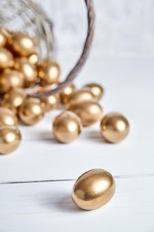 Ovos de páscoa de ouro derramados de uma cesta de vime na mesa de madeira branca