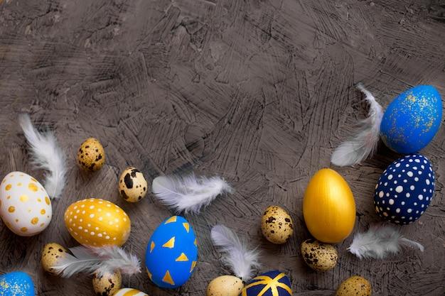 Ovos de páscoa de ouro e azul com penas