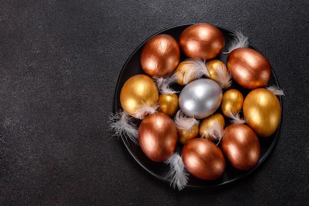 Ovos de páscoa de ouro e bronze e bolo de páscoa. preparação para o feriado