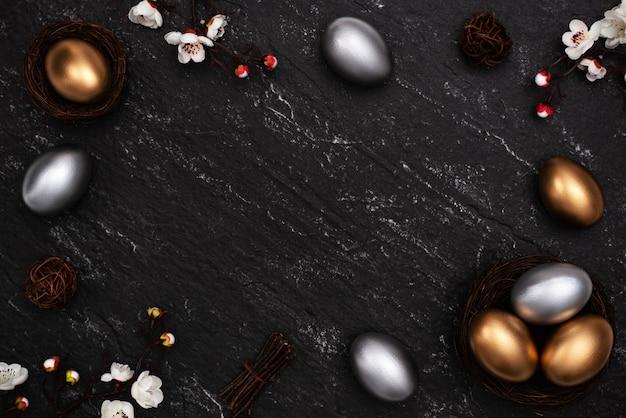 Ovos de páscoa de ouro e prata com flor de ameixa em fundo de mesa de ardósia preto escuro.