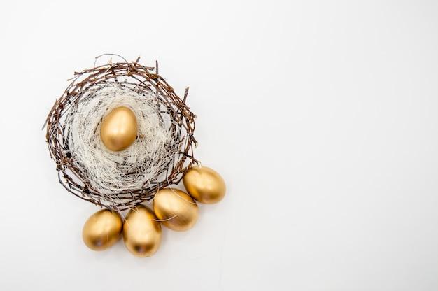 Ovos de páscoa de ouro em uma caixa com estrelas douradas sobre fundo branco