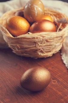 Ovos de páscoa de ouro na mesa de madeira