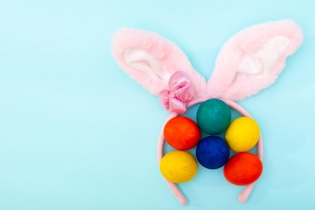 Ovos de páscoa de pintados à mão e orelhas de coelho rosa sobre uma superfície azul, copie o espaço, vista superior, plana leigos.