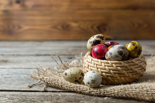 Ovos de páscoa de pintados à mão em uma cesta de vime em guardanapo de serapilheira com fundo de madeira de pintados à mão.