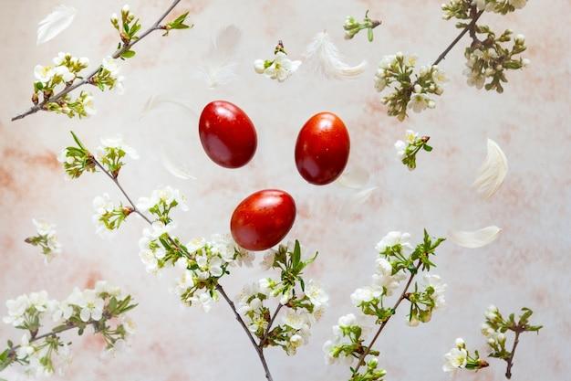 Ovos de páscoa de tintura natural vermelha e flores de primavera com penas em levitação de fundo bege pastel