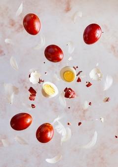 Ovos de páscoa de tintura natural vermelha voando com penas sobre fundo bege pastel. vertical