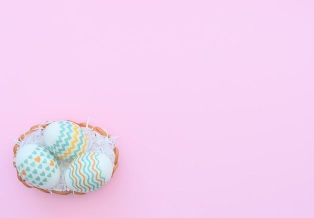 Ovos de páscoa decorados caem na cesta em rosa