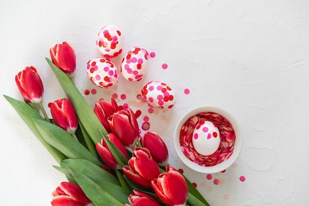 Ovos de páscoa decorados com confetes de papel e tulipas