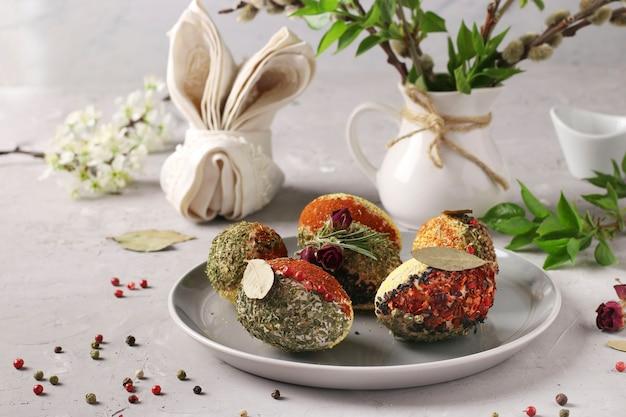 Ovos de páscoa decorados com diferentes especiarias e cereais, sem corantes e conservantes, em um prato sobre um fundo cinza de concreto.