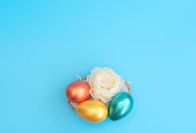 Ovos de páscoa decorados ficam na cesta como um ninho com uma flor branca em azul