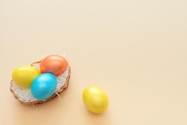 Ovos de páscoa decorados ficam na cesta como um ninho em amarelo