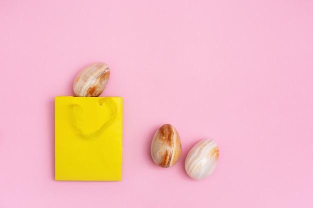 Ovos de páscoa decorativos de ônix de pedra preciosa e bolsa de presente amarela brilhante. conceito de férias da primavera.