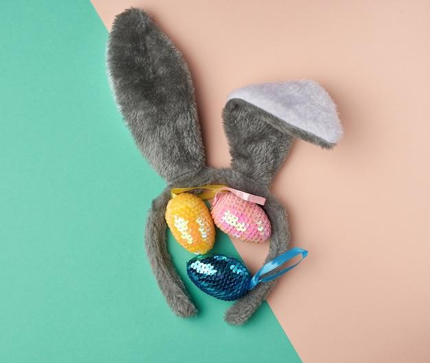 Ovos de páscoa decorativos multicoloridos, decorados com lantejoulas e máscara de coelho na cabeça com orelhas