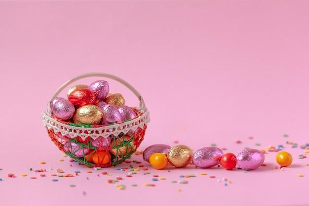 Ovos de páscoa doce doces na cesta em rosa