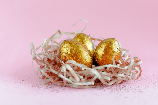 Ovos de páscoa dourado decorados no ninho em fundo rosa. espaço mínimo da cópia do conceito de easter para o texto.