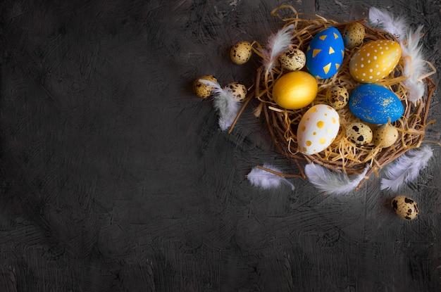 Ovos de páscoa dourados e azuis em um ninho com penas