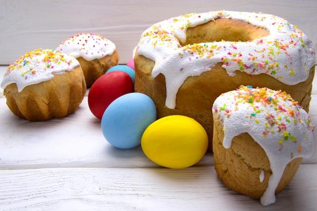 Ovos de páscoa e bolo de páscoa diferente na mesa de madeira branca