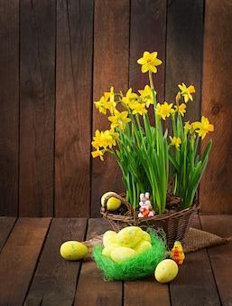 Ovos de páscoa e flores em uma mesa de madeira escura