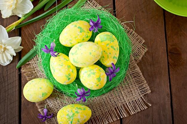 Ovos de páscoa e flores na mesa de madeira