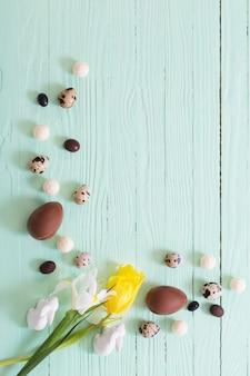 Ovos de páscoa e flores na superfície de madeira verde
