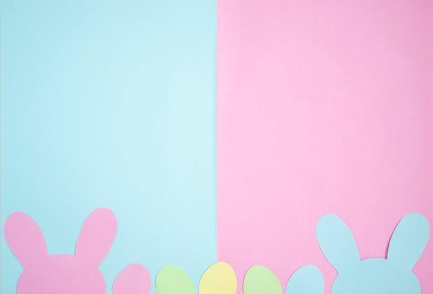 Ovos de páscoa e orelhas de coelho são feitos de papel. composição em tons pastel de rosa e azul