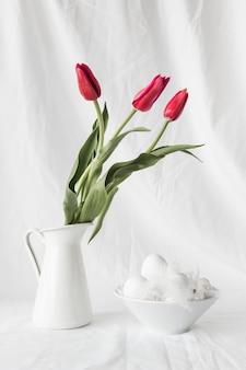 Ovos de páscoa e penas na tigela perto de ramo de flores em vaso