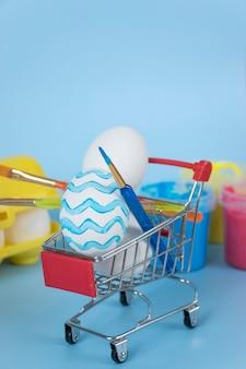 Ovos de páscoa e pincéis no carrinho de compras com tintas e bandeja de ovos em fundo azul. feliz feriado de páscoa.
