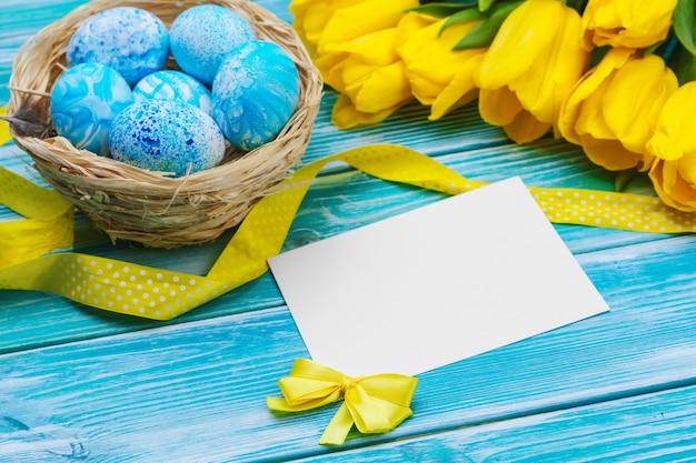 Ovos de páscoa e tulipas. decoração festiva na mesa de madeira. cartão com espaço de cópia
