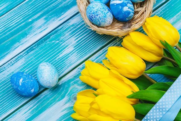 Ovos de páscoa e tulipas. decoração festiva na mesa de madeira