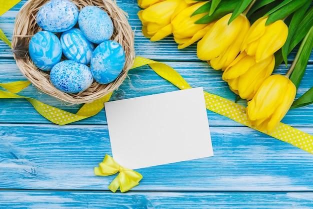 Ovos de páscoa e tulipas. decoração festiva no fundo de madeira.