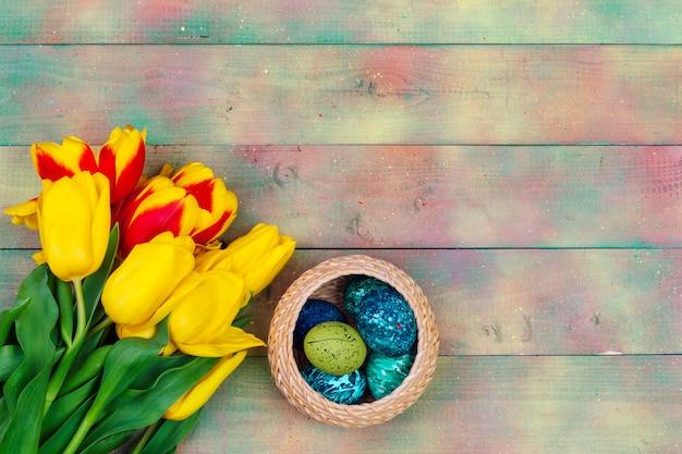 Ovos de páscoa e tulipas em fundo de pranchas de madeira