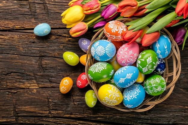 Ovos de páscoa e tulipas em pranchas de madeira