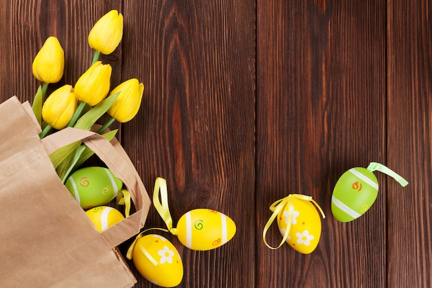 Ovos de páscoa e tulipas em saco de papel
