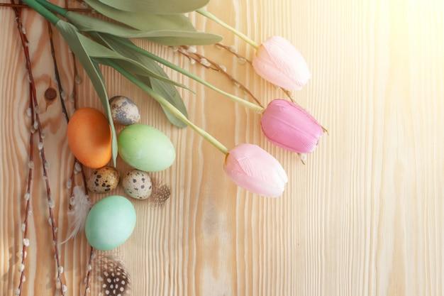 Ovos de páscoa e tulipas em uma mesa de madeira. luz da manhã.