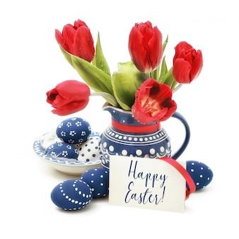 Ovos de páscoa e tulipas vermelhas em cerâmica azul sobre branco, texto