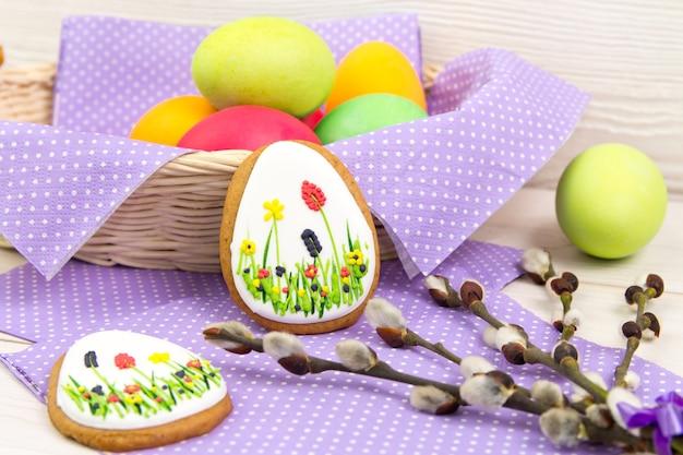 Ovos de páscoa e um galho de salgueiro na mesa de madeira
