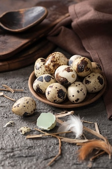 Ovos de páscoa em ângulo alto no prato com tecido e colher de pau