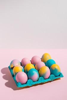 Ovos de páscoa em grande cremalheira na mesa-de-rosa