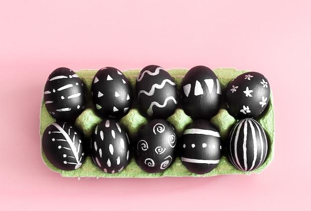 Ovos de páscoa em preto em uma mesa colorida rosa