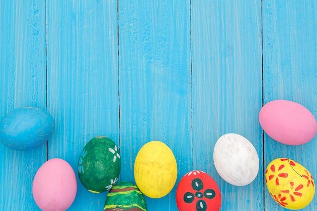 Ovos de páscoa em tons pastel na mesa de madeira
