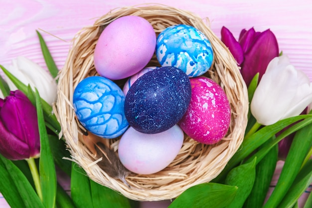 Ovos de páscoa em um ninho e tulipas em pranchas de madeira