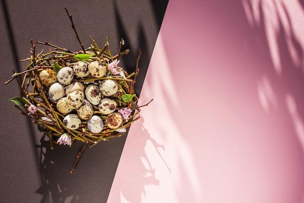 Ovos de páscoa em um ninho em um fundo rosa e preto conceito mínimo de páscoa vista superior do espaço de cópia