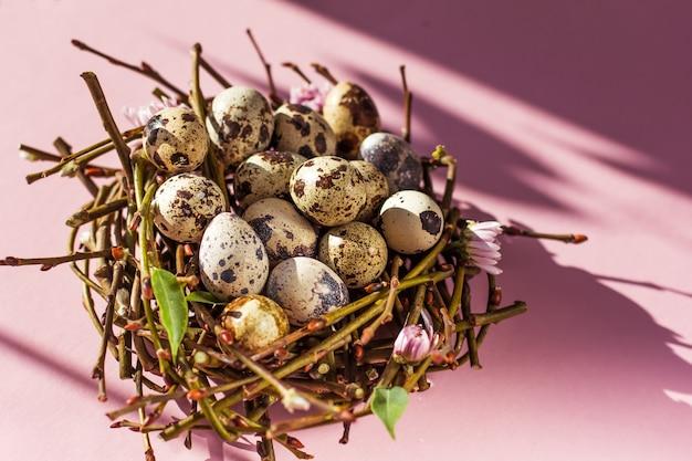 Ovos de páscoa em um ninho em um fundo rosa o conceito mínimo de páscoa. espaço de cópia da vista superior
