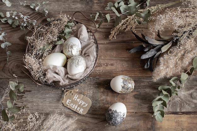 Ovos de páscoa em uma cesta decorativa com flores secas em uma mesa de madeira. conceito de feliz páscoa.