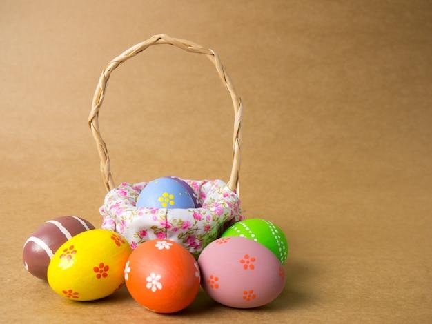 Ovos de páscoa em uma cesta tecer madeira no canto esquerdo no marrom