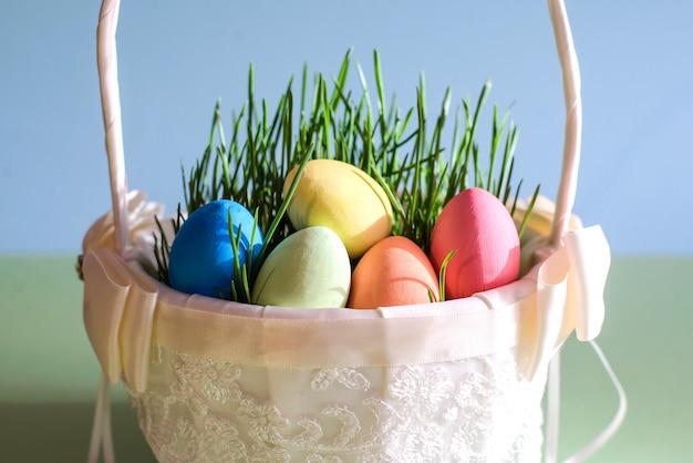 Ovos de páscoa em uma linda cesta branca com grama verde